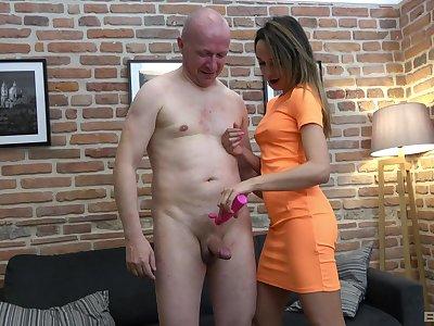 Brunette hottie in an orange dress sucks and strokes an older man